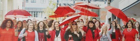 Celebrating 30 years of the New Zealand Prostitutes Collective, a group of people wearing red, hold up umbrellas and smile for the camera.